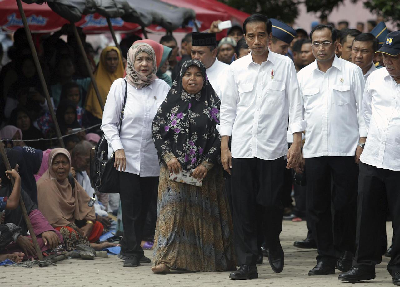 Indonesia's President Joko Widodo, third from right, walks with, from left to right; Health Minister Nila Moeloek, unidentified earthquake survivor, Transportation Minister Budi Karya Sumadi and Public Works and Housing Minister Basuki Hadimuljono during his visit to a temporary shelter in Tringgading, Aceh province, Indonesia, Friday, Dec. 9, 2016. Widodo traveled Friday to areas of Aceh province devastated by a magnitude 6.5 earthquake, as estimates of the number of displaced people swelled, and vowed that torn-apart communities would be rebuilt. (AP Photo/Heri Juanda)