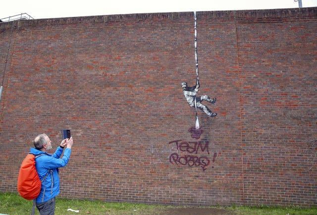The Banksy artwork which was painted on the side of the former prison in Reading has now been defaced