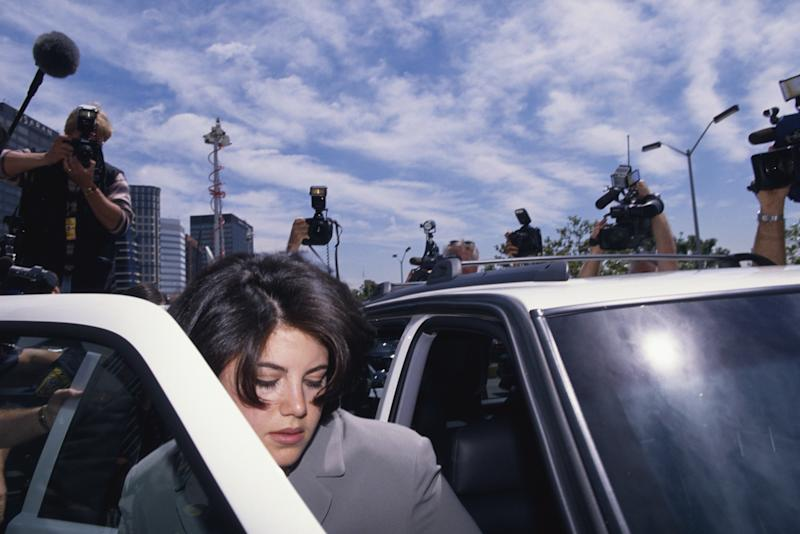 Monica Lewinsky surrounded by photographers as she gets into car in 1998. Lewinsky is on her way to the FBI Headquarters.