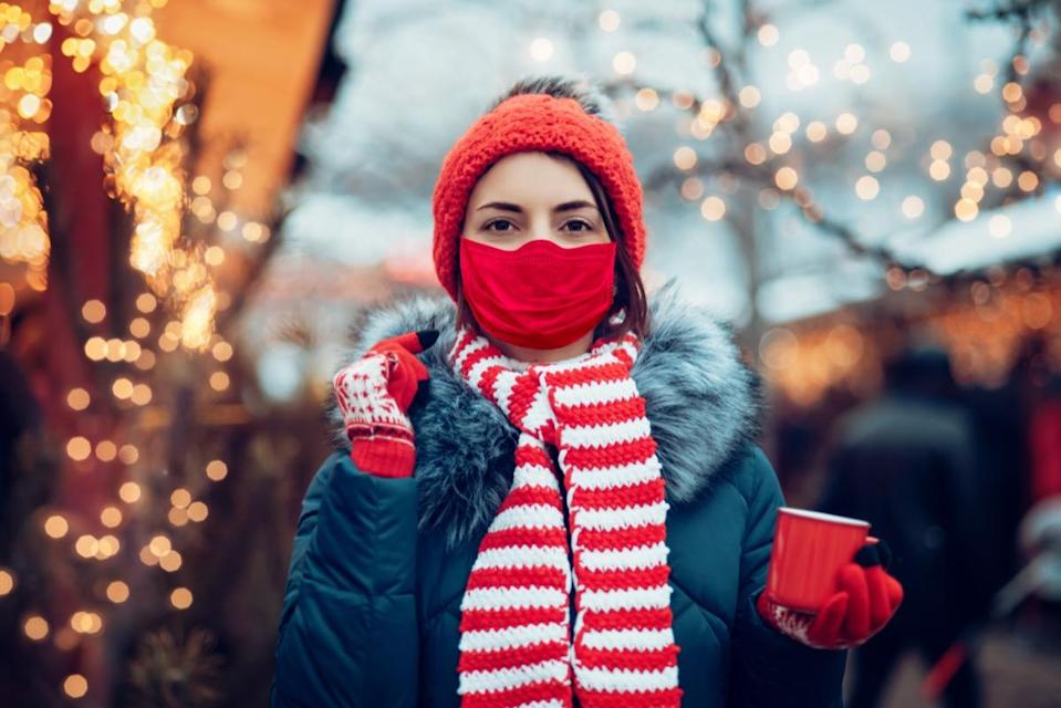 woman drinking punch on christmas market wearing medicine mask.