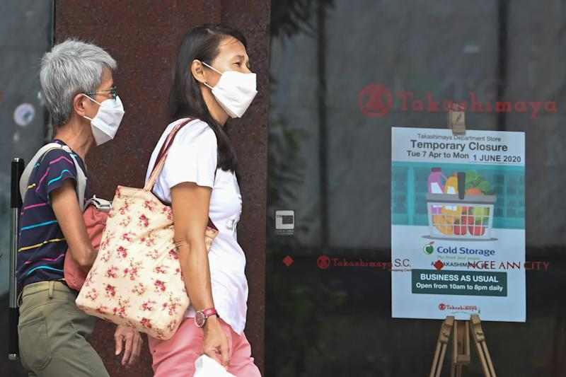 People, wearing face masks as a preventive measure against the spread of the COVID-19 novel coronavirus, walk past a closed retail mall along the Orchard Road shopping belt in Singapore on May 6, 2020. (Photo by Roslan RAHMAN / AFP) (Photo by ROSLAN RAHMAN/AFP via Getty Images)