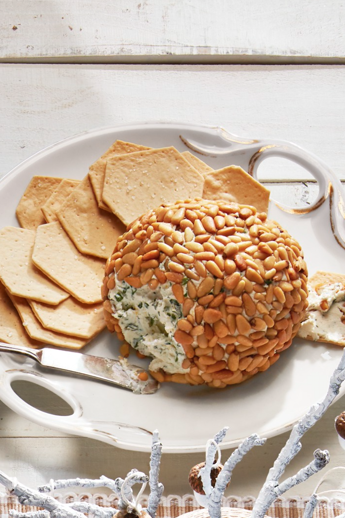 "<p>And what better pairing for the crackers than this cheese ball packed with flavorful herbs and coated in crunchy pine nuts?</p><p><strong><a href=""https://www.countryliving.com/food-drinks/a29641000/herbed-cheese-ball-recipe/"" rel=""nofollow noopener"" target=""_blank"" data-ylk=""slk:Get the recipe"" class=""link rapid-noclick-resp"">Get the recipe</a>.</strong> </p><p><a class=""link rapid-noclick-resp"" href=""https://www.amazon.com/Rubbermaid-Ultimate-Party-Serving-white/dp/B01IA4FW50/?tag=syn-yahoo-20&ascsubtag=%5Bartid%7C10050.g.34553078%5Bsrc%7Cyahoo-us"" rel=""nofollow noopener"" target=""_blank"" data-ylk=""slk:SHOP PORTABLE APPETIZER TRAYS"">SHOP PORTABLE APPETIZER TRAYS</a> </p>"