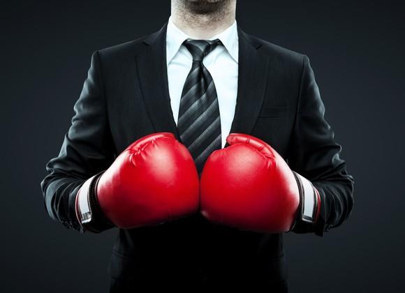 A businessman in a suit wearing boxing gloves.