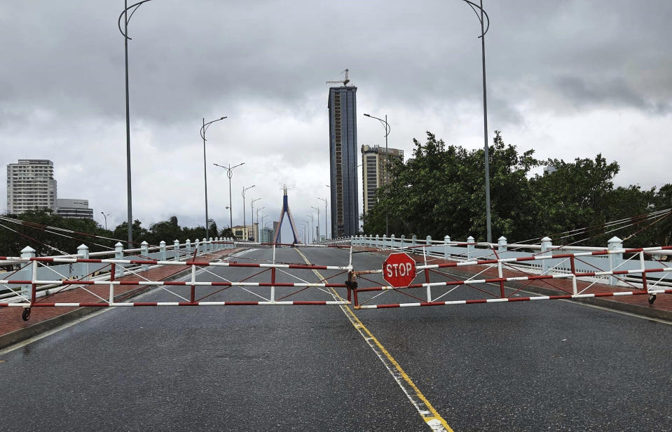 An empty street is barricaded ahead of Typhoon Molave in Da Nang, Vietnam Wednesday, Oct. 28, 2020. Typhoon Malove sank a few fishing boats as it approached Vietnam's south central coast on Wednesday morning. (Vo Van Dung/VNA via AP)
