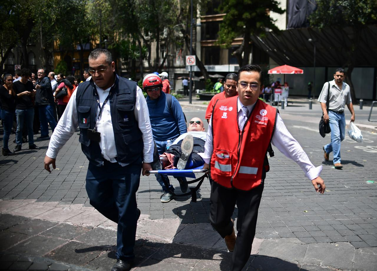 <p>A man is assisted in Mexico City after a real quake rattled the country on September 19, 2017 as an earthquake drill was being held in the capital. (Photo: Ronaldo Schemidt/AFP/Getty Images) </p>