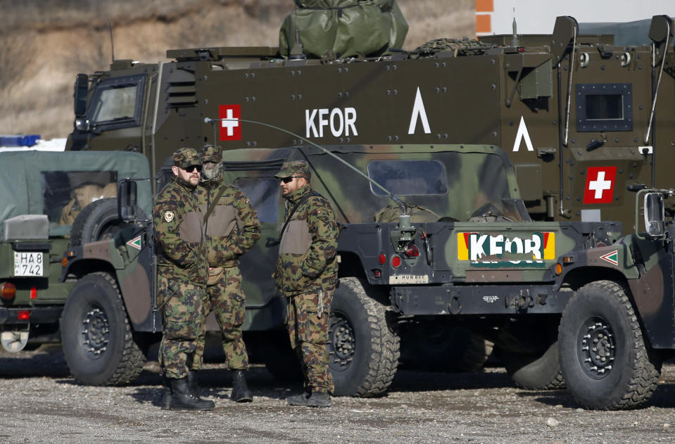 Soldiers of NATO-led peacekeeping force KFOR take a break by the side of the road near the village of Leposavic, northern Kosovo, Thursday, Dec. 13, 2018. In Friday's vote, Kosovo's 120-seat parliament is expected to approve three draft laws to turn an existing paramilitary force into a lightly armed army. (AP Photo/Darko Vojinovic)