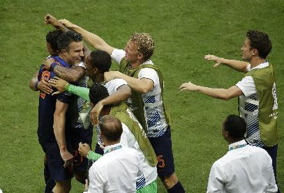 Netherlands' Robin van Persie celebrates with bench teammates during the group B World Cup soccer match between Spain and the Netherlands at the Arena Ponte Nova in Salvador, Brazil, Friday, June 13, 2014. (AP Photo/Christophe Ena)
