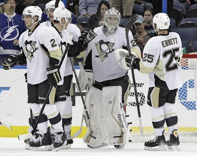 Pittsburgh Penguins goalie Marc-Andre Fleury (29), center, celebrates with teammates, Andrew Ebbett (25) and Matt Niskanen (2) after an NHL hockey game against the Tampa Bay Lightning, Friday, Nov. 29, 2013, in Tampa, Fla. The Penguins won 3-0. (AP Photo/Chris O'Meara)