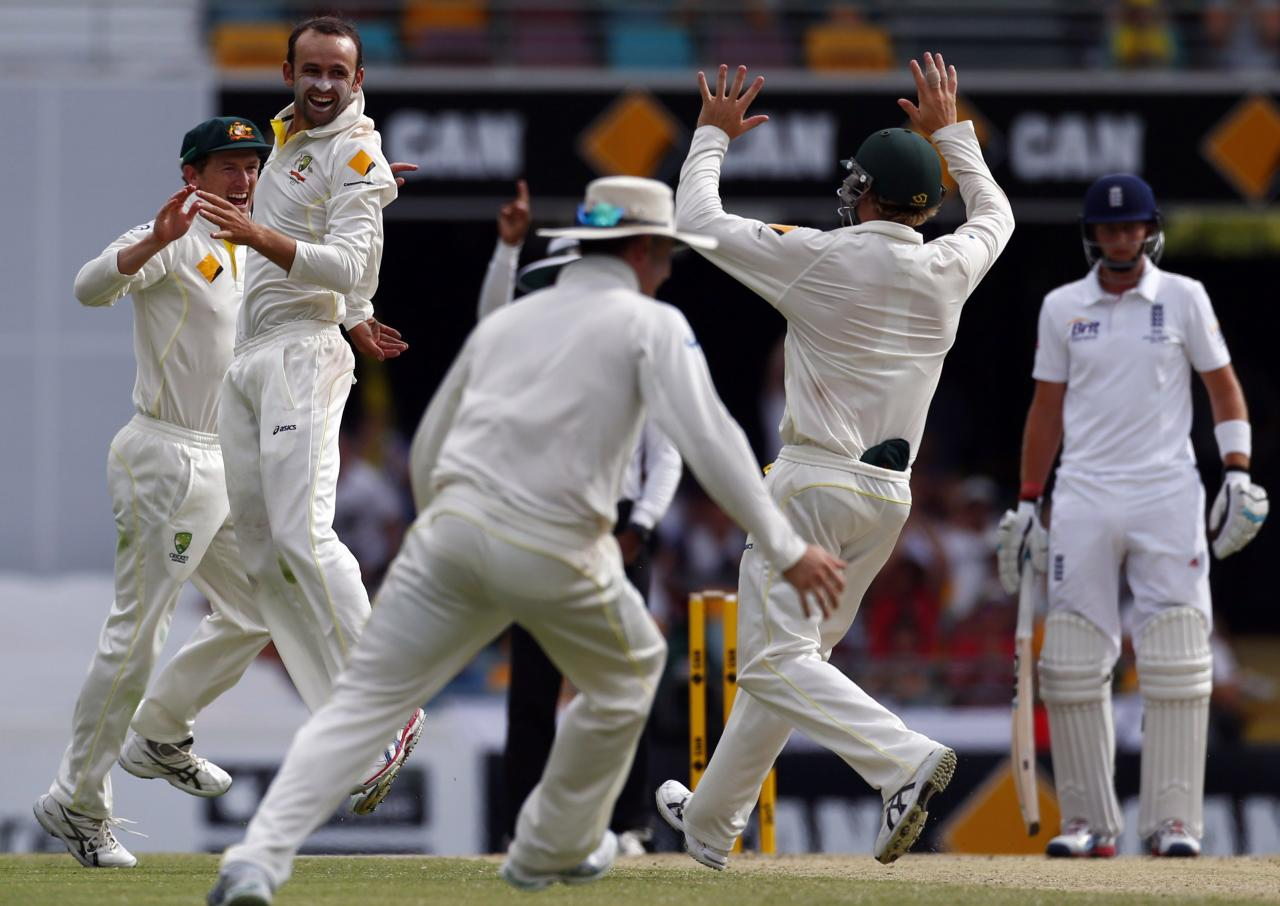 Australia's Nathan Lyon (2nd L) celebrates with George Bailey (L) after he took the wicket of England's captain Alastair Cook during the fourth day's play of the first Ashes cricket test match in Brisbane November 24, 2013. REUTERS/David Gray (AUSTRALIA - Tags: SPORT CRICKET)