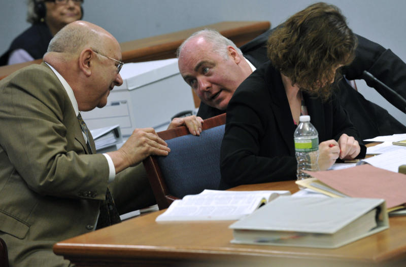 Michael Skakel leans around Jessica Santos to talk to his lead defense attorney Hubert Santos at Skakel's habeas corpus trial at State Superior Court in Vernon, Conn., on Monday, April 22, 2013. Skakel's attorneys are challenging his 2002 murder conviction. (AP Photo/The Stamford Advocate,Jason Rearick, Pool)