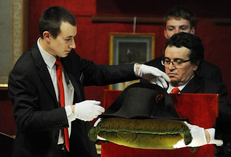 An auction house employee displays one of Napoleon's famous two-pointed hats in the Osenat auction house in Fontainebleau on November 16, 2014 (AFP Photo/Dominique Faget)