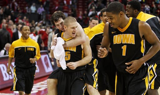 Iowa's Stephan McCarty, left, Zach McCabe, Matt Gatens (5) and Melsahn Basabe (1) celebrate after defeating Wisconsin 72-65 in an NCAA college basketball game Saturday, Dec. 31, 2011, in Madison, Wis. (AP Photo/Andy Manis)