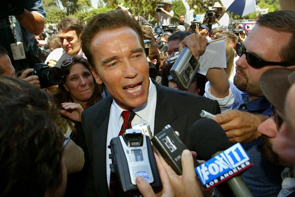 Arnold Schwarzenegger talks to reporters as he leaves the Los Angeles county registrar's office carrying the papers needed to run for governor, in 2003.