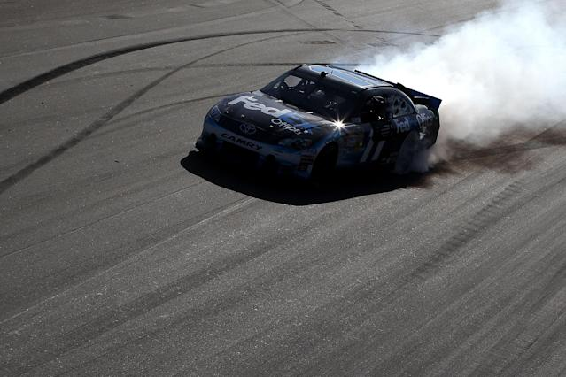 AVONDALE, AZ - MARCH 04: Denny Hamlin, driver of the #11 FedEx Office Toyota, celebrates with a burn out after winning the NASCAR Sprint Cup Series SUBWAY Fresh Fit 500 at Phoenix International Raceway on March 4, 2012 in Avondale, Arizona. (Photo by Christian Petersen/Getty Images)