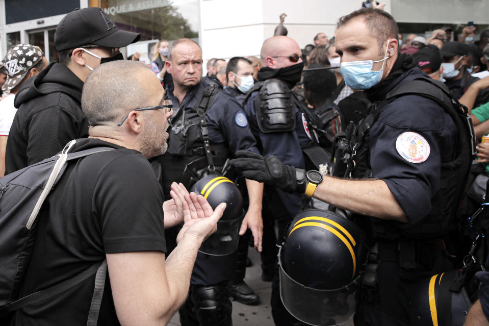 A riot police officer gestures while speaking to a demonstrator during a protest in memory of Lamine Dieng, a 25-year-old Franco-Senegalese who died in a police van after being arrested in 2007, in Paris, Saturday, June 20, 2020. Multiple protests are taking place in France on Saturday against police brutality and racial injustice, amid weeks of global anger unleashed by George Floyd's death in the US. (AP Photo/Christophe Ena)