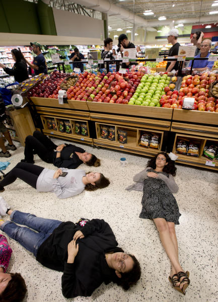 "Demonstrators lie on the floor at a Publix Supermarket in Coral Springs, Fla., Friday, May 25, 2018. Students from the Florida high school where 17 people were shot and killed earlier this year did a ""die in"" protest at a supermarket chain that backs a gubernatorial candidate allied with the National Rifle Association. Shortly before the the ""die-in"" Publix announced that it will suspend political donations. (AP Photo/Wilfredo Lee)"
