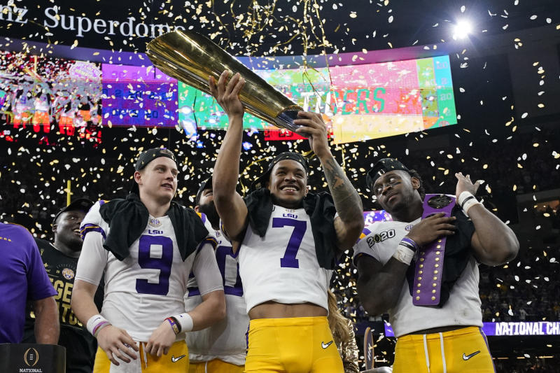 LSU safety Grant Delpit holds the trophy as quarterback Joe Burrow, left, and linebacker Patrick Queen look on after a NCAA College Football Playoff national championship game against Clemson, Monday, Jan. 13, 2020, in New Orleans. LSU won 42-25. (AP Photo/David J. Phillip)