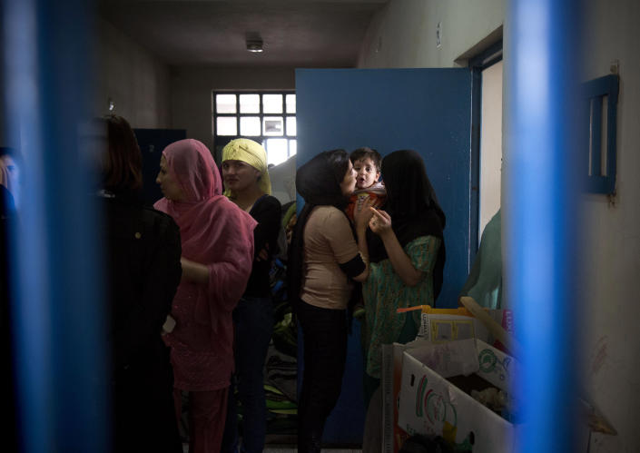 """Picture taken March 28, 2013 shows an Afghan female prisoner kissing her child inside her prison tract in Badam Bagh, Afghanistan's central women's prison, in Kabul, Afghanistan. 202 women living in the six- year- old jail, the majority of the women are serving sentences of up to seven years for leaving their husbands, refusing to accept a marriage arranged by their parents, or choosing to leave their parent's home with a man of their choice, all so-called """"moral"""" crimes(. AP Photo/Anja Niedringhaus)"""