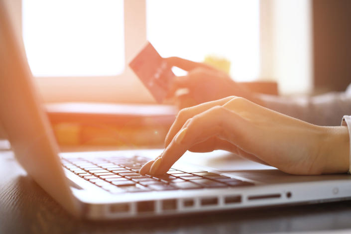 Woman's hand hovers over a laptop keyboard while the other holds a credit card