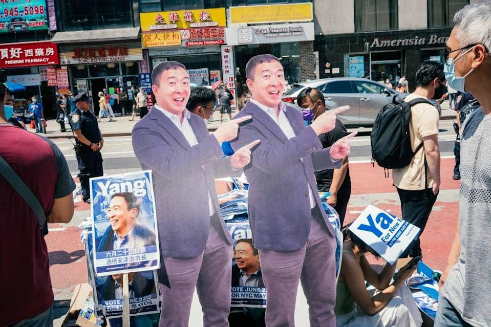 Two life-sized cardboard cutouts pointing with both hands and smiling