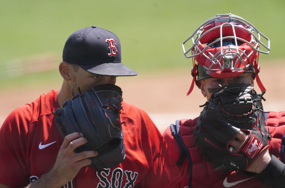 Boston Red Sox starting pitcher Nathan Eovaldi, left, talks with catcher Christian Vazquez as they walk off the field at the end of the second inning of a spring training baseball game against the Tampa Bay Rays, Friday, March 19, 2021, in Fort Myers, Fla.. (AP Photo/John Bazemore)