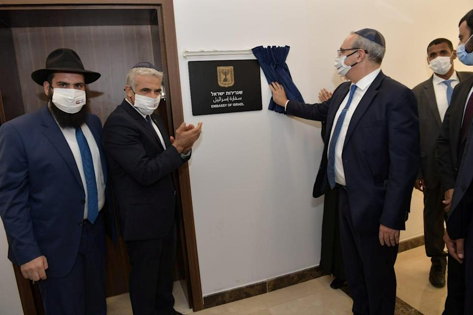 Israeli Foreign Minister Yair Lapid applauds as a plaque is revealed during an inauguration ceremony of Israel's embassy in Abu Dhabi, United Arab Emirates, on Tuesday (VIA REUTERS)