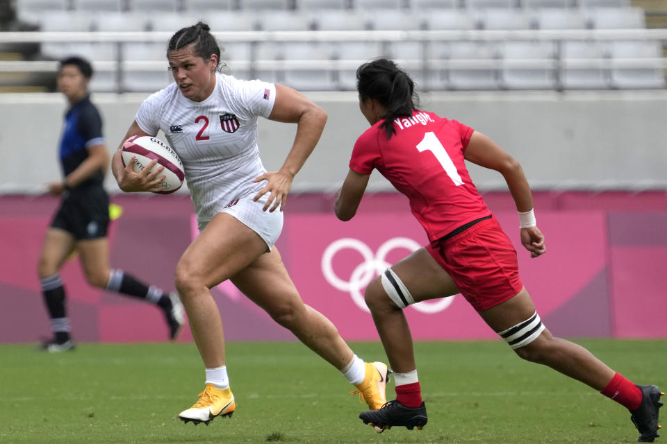 Ilona Maher, left, of the United States is chased by China's Yang Min during their women's rugby sevens match at the 2020 Summer Olympics, Thursday, July 29, 2021, in Tokyo. (AP Photo/Shuji Kajiyama)