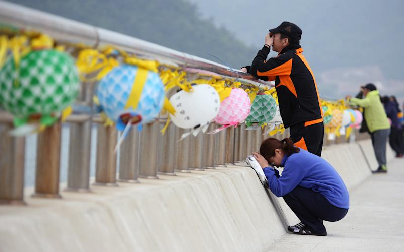 Relatives of a passenger aboard the sunken ferry Sewol weep at a port in Jindo, South Korea, Thursday, May 8, 2014. South Korean prosecutors said they have detained the head of the company that owns the ferry that sank last month over an allegation of cargo overloading.(AP Photo/Yonhap) KOREA OUT