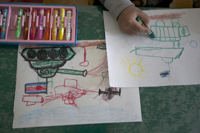 In this photo taken on Friday, April 27, 2012, a North Korean child draws tanks and weapons during an art class at the Kaeson Kindergarten in Pyongyang, North Korea. For North Koreans, the systematic indoctrination of anti-Americanism starts as early as kindergarten and is as much a part of the curriculum as learning to count. (AP Photo/Vincent Yu)