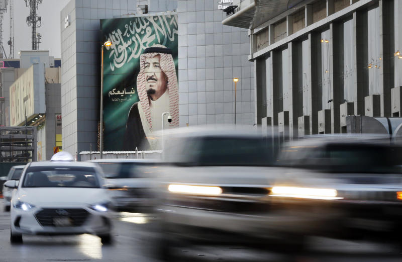 "In this picture taken with low shutter speed, vehicles passes in front of a banner showing Saudi King Salman, with Arabic that reads ""We pledge you to listen and obey"" at a shopping mall, in Riyadh, Saudi Arabia, Thursday, Sept. 19, 2019. Any attack on Iran by the U.S. or Saudi Arabia will spark an ""all-out war,"" Tehran's top diplomat warned Thursday, raising the stakes as Washington and Riyadh weigh a response to a drone-and-missile strike on the kingdom's oil industry that shook global energy markets. (AP Photo/Amr Nabil)"