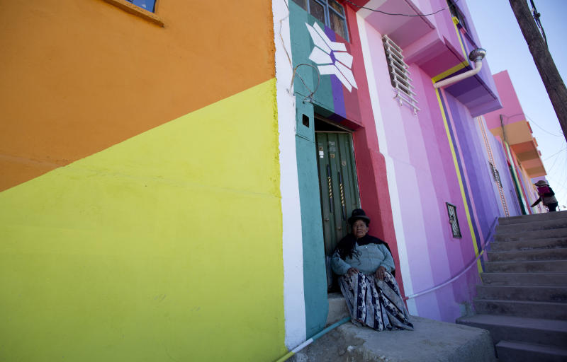 "In this May 31, 2019 photo, a resident sits on her door stoop in the Chualluma neighborhood, in La Paz, Bolivia. Chaulluma is located about 12,500 feet (3,800 meters) above sea level and it's reached by a steep staircase known ominously as ""The 1,000 steps."" (AP Photo/Juan Karita)"