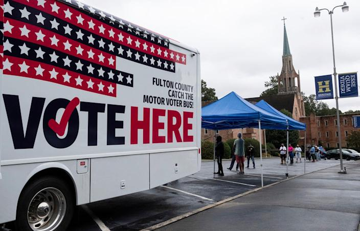 One of Fulton County's two mobile voting stations sits in the parking lot of Morningside Baptist Church on Monday morning, Oct. 12, 2020 for the first day of early voting. Election officials are increasingly worried about voter intimidation on Election Day. (Ben Gray/Atlanta Journal-Constitution via AP)