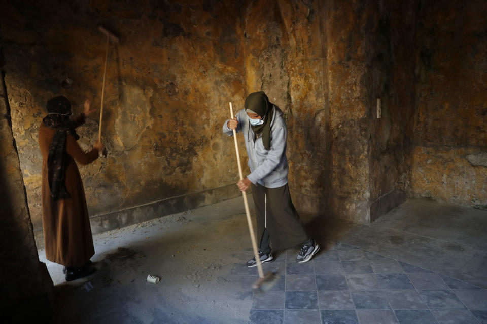 Female artist volunteers renovate a room of the long-abandoned 200-year-old al-Kamalaia school, in the old quarter of Gaza City, Sunday, Dec. 20, 2020. Less than 200 of these old buildings are still partly or entirely standing, according to officials and they are threatened by neglect, decaying and urban sprawl. (AP Photo/Adel Hana)