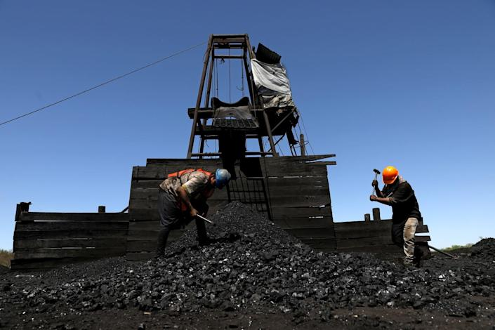 Miners break up pieces of coal.