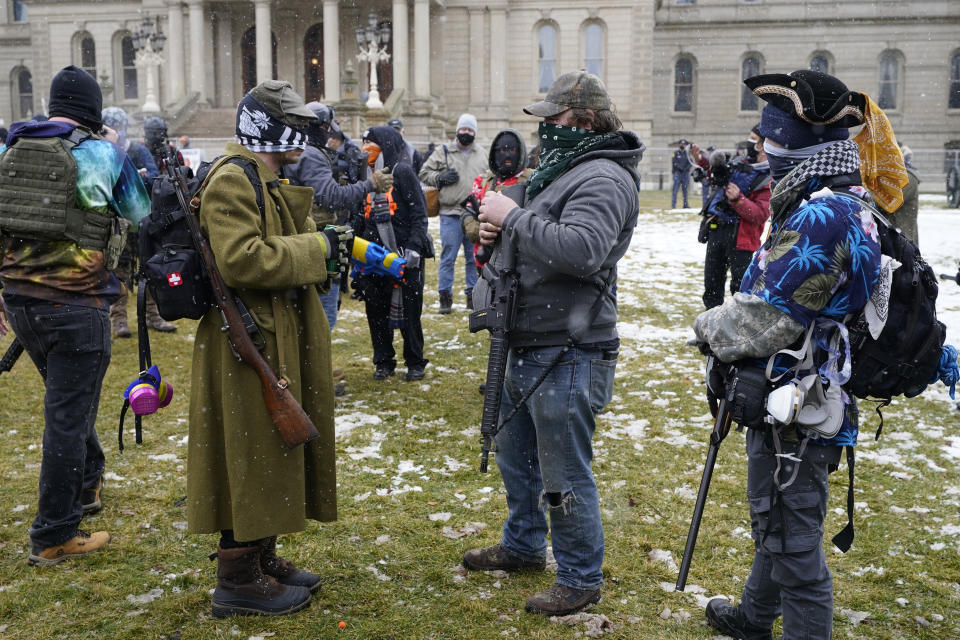 Men with rifles stand outside the State Capitol, Sunday, Jan. 17, 2021, in Lansing, Mich. (AP Photo/Carlos Osorio)