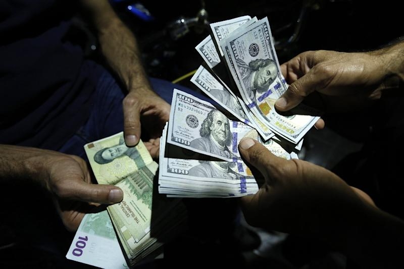 A man exchanges Iranian rials and US dollars at an exchange bureau in Tehran on August 8, 2018