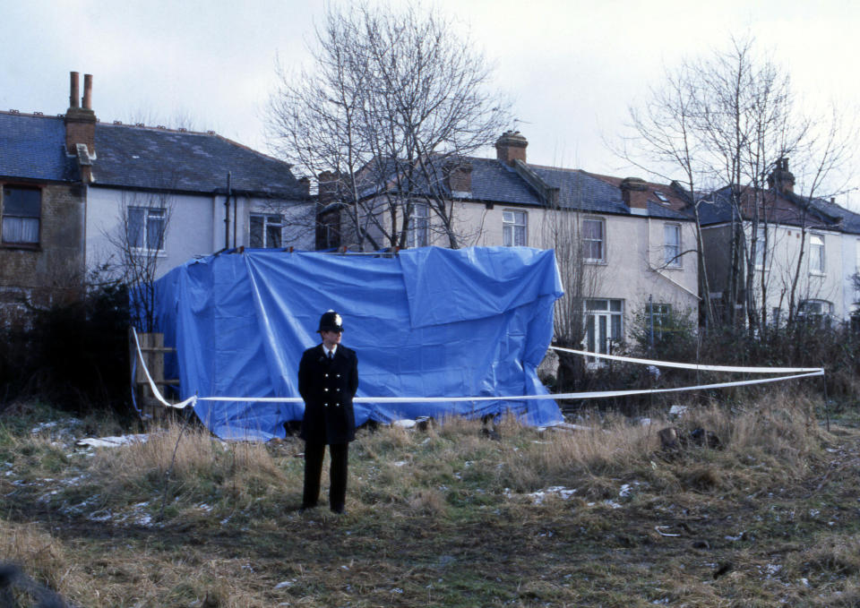 A London policeman stands guard near a canopy erected on the garden of the North London home of Dennis Nilsen, on Feb. 13, 1983, as policemen inside dig the soil in search of the remains of human bodies believed to have been buried there. Police say there could be the remains of up to 13 murder victims buried in the area. The house is in Melrose Avenue, Willesden Green. (AP Photo/John Redman)