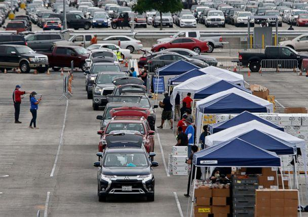 PHOTO: People wait in line to get food at the San Antonio Food Bank distribution center being held in the parking lot at the Alamo Dome in San Antonio, April 17, 2020.  (Larry W Smith /EPA via Shutterstock)
