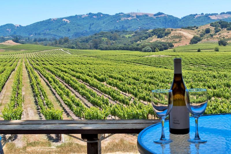 A bottle of wine sits on a table in front of vineyards and mountains in Sonoma