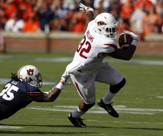 Auburn defensive back Trovon Reed (25) pulls down Arkansas running back Jonathan Williams (32) for a loss during the first half of an NCAA college football game on Saturday, Aug. 30, 2014, in Auburn, Ala. (AP Photo/Butch Dill)
