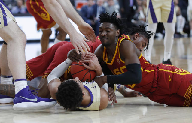 Washington's Matisse Thybulle, bottom left, and Southern California's Jonah Mathews fight for the ball during the first half of an NCAA college basketball game in the quarterfinal round of the Pac-12 men's tournament Thursday, March 14, 2019, in Las Vegas. (AP Photo/John Locher)
