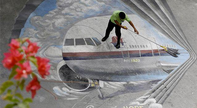 a school utility worker mops a mural depicting the missing Malaysia Airlines Flight 370 Tuesday, April 8, 2014 at the Benigno