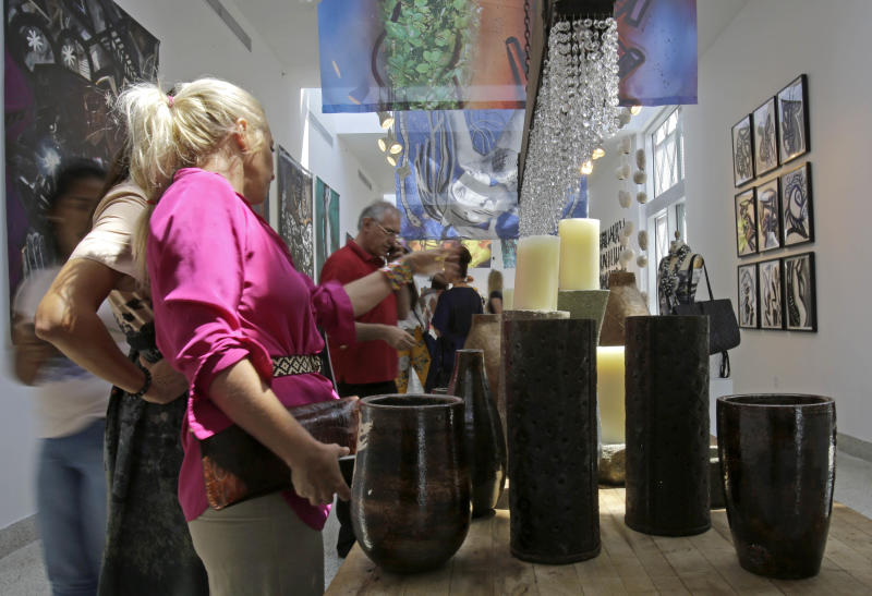 Visitors check art, furnishing and accessories at the Discover Haiti Exhibition in the Little Haiti area of Miami, Friday, May 17, 2013. (AP Photo/Alan Diaz)