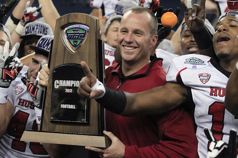 Northern Illinois coach Dave Doeren holds the Mid-American Conference championship trophy after his team defeated Kent State 44-37 in double overtime in an NCAA college football game, Friday, Nov. 30, 2012 in Detroit. (AP Photo/Carlos Osorio)