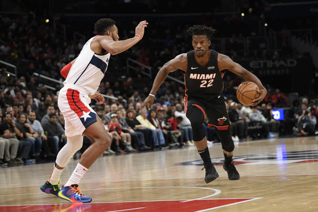 Miami Heat forward Jimmy Butler (22) dribbles the ball against Washington Wizards forward Troy Brown Jr. (6) during the first half of an NBA basketball game, Sunday, March 8, 2020, in Washington. (AP Photo/Nick Wass)