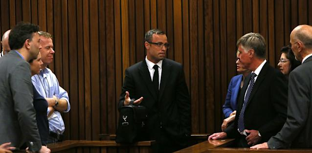 Oscar Pistorius, center, speaks with family and friends, right, as press, left, look on, as the prosecution wrapped up it's case in Pretoria, South Africa, Tuesday, March 25, 2014. Pistorius is charged with the Valentines Day 2013 shooting death of his girlfriend Reeva Steenkamp. (AP Photo/Esa Alexander, Pool)