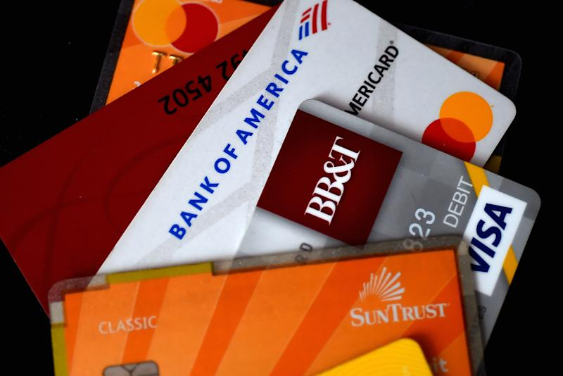 This illustration picture shows debit and credit cards arranged on a desk on April 6, 2020 in Arlington, Virginia - As restaurants risk dramatic drops in sales or outright closure amid the COVID-19 pandemic, some businesses are encouraging customers to pay with credit or debit card, while others are introducing no cash policies to limit the exchange of germs during transactions. (Photo by Olivier DOULIERY / AFP) (Photo by OLIVIER DOULIERY/AFP via Getty Images)