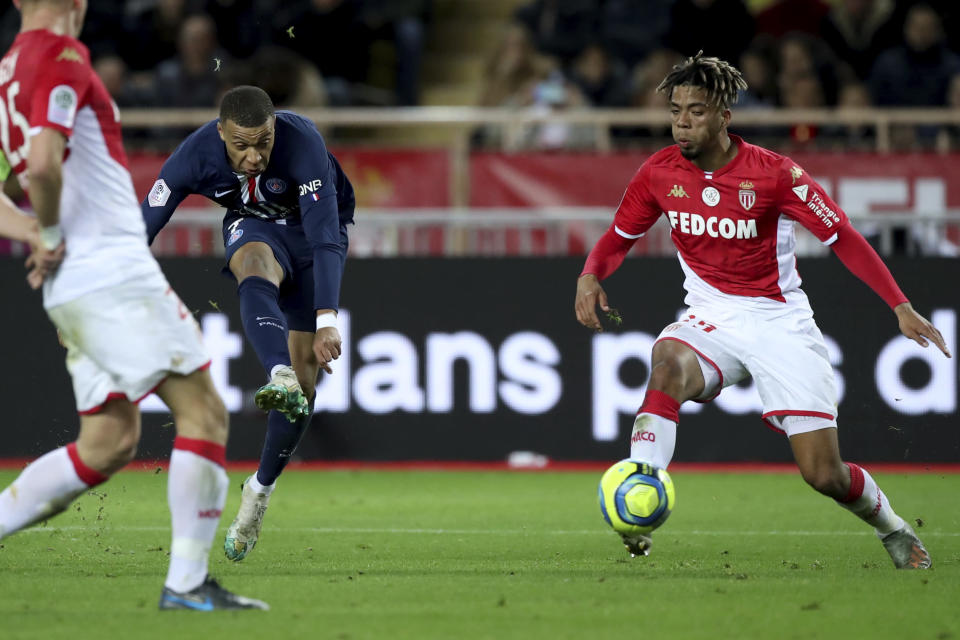 PSG's Kylian Mbappe, left, shoots during the French League One soccer match between Monaco and Paris Saint-Germain at the Louis II stadium in Monaco, Wednesday, Jan. 15, 2019. (AP Photo/Daniel Cole)