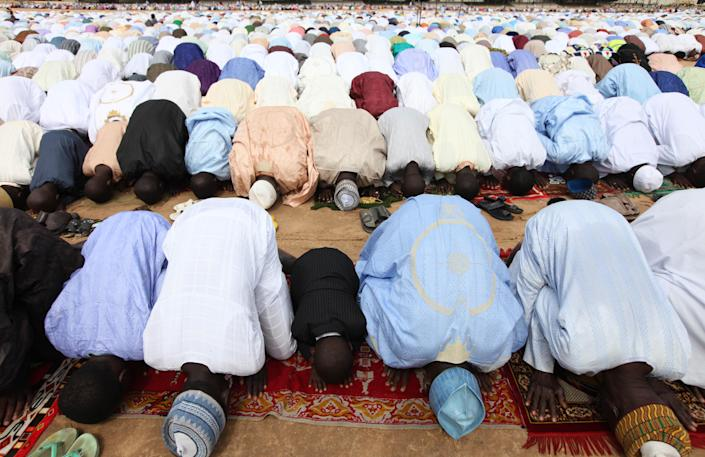 """Nigeria muslims offer their prayers during Eid al-Fitr at Ramat square in Maiduguri, Nigeria, Thursday, Aug. 8, 2013. Nigerians in the birthplace of an Islamic uprising gripping the northeast celebrated the Muslim holy day of Eid al-Fitr on Thursday with devout prayers and a joyful show of adulation for their king that attracted more than 10,000 people. It was the first durbar in three years in the city of Maiduguri and the joy that it could take place - albeit amid massive security - was heard in the cries of ululating women, screams of delight from children and men chanting """"Long live the king!"""" (AP Photo/Sunday Alamba)"""