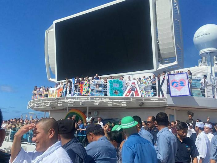 Cruise ship workers gather on the deck of the Sky Princess to display a large sign that reads 'We will be back' days after the cruising industry came to a halt March 12, 2020. Gan Sungaralingum, a watch salesman onboard Sky Princess, spent 170 days stuck at sea, trying to get back home to the island of Mauritius, during a global pandemic.